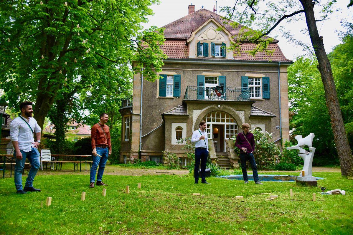 Das Corpshaus im Hintergrund. Im Vordergrund Mitglieder der Verbindung beim Spielen von Wikingerschach in einem schönen Garten.